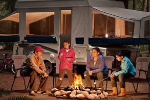 family enjoying a campfire beside their pop-up tent
